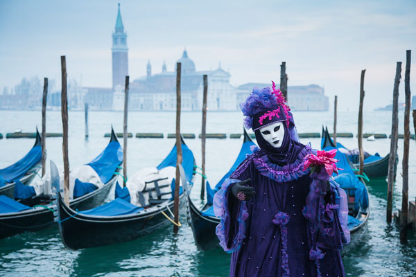 Costumed person in front of gondolas, Venice, Italy